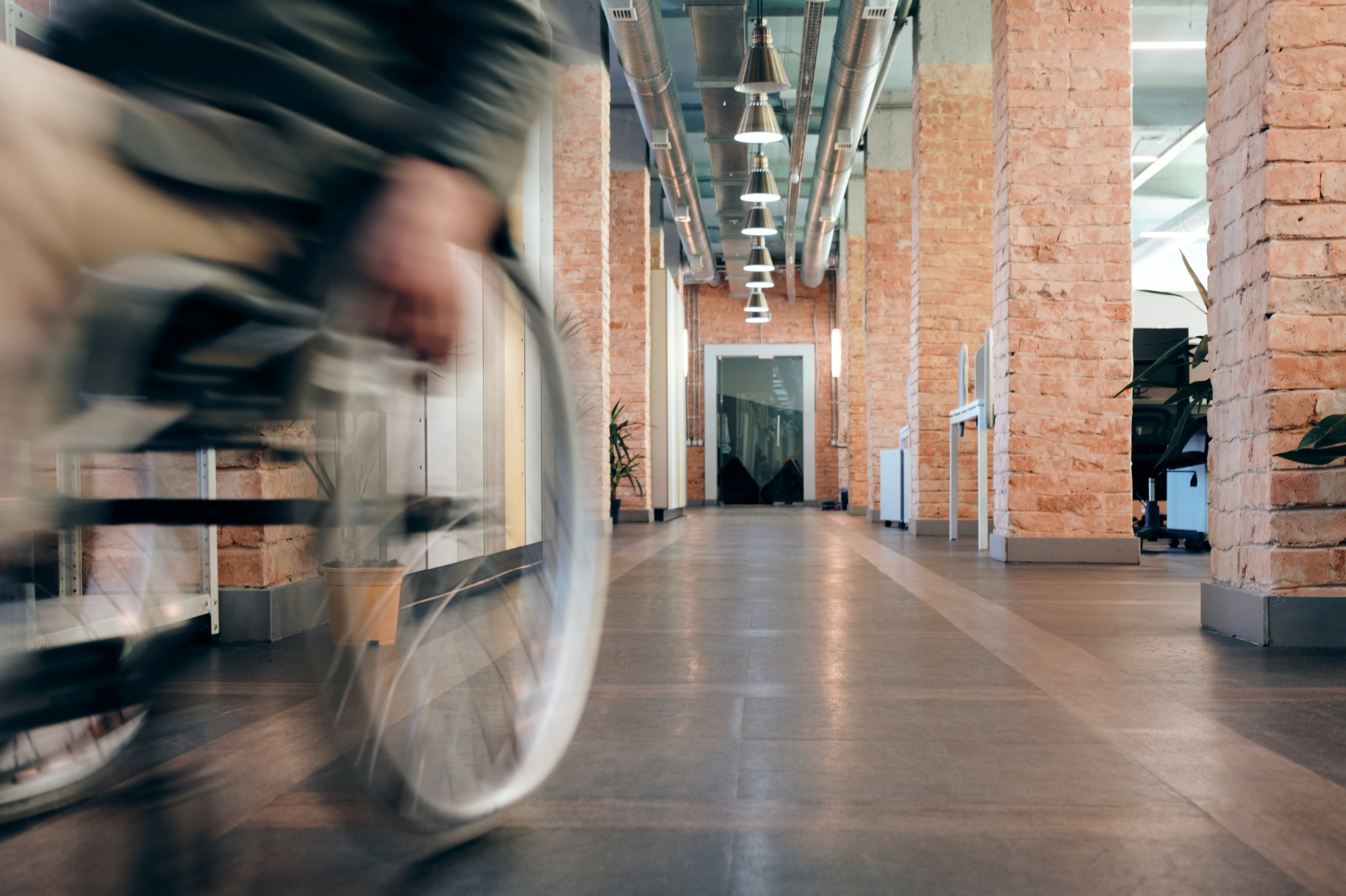 Person in wheelchair moving down hallway of office