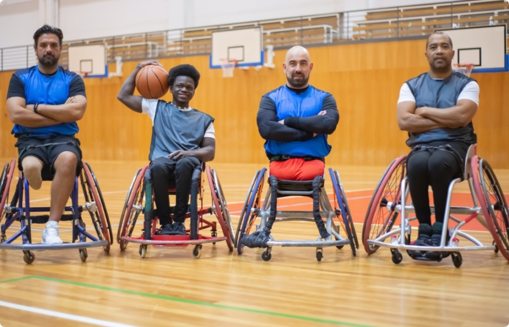 Group of 4 men in wheelchairs playing basketball and posing for a team photograph..