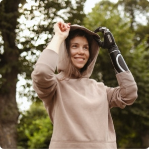 Smiling woman pulling up her hooded sweatshirt with a prosthetic arm.