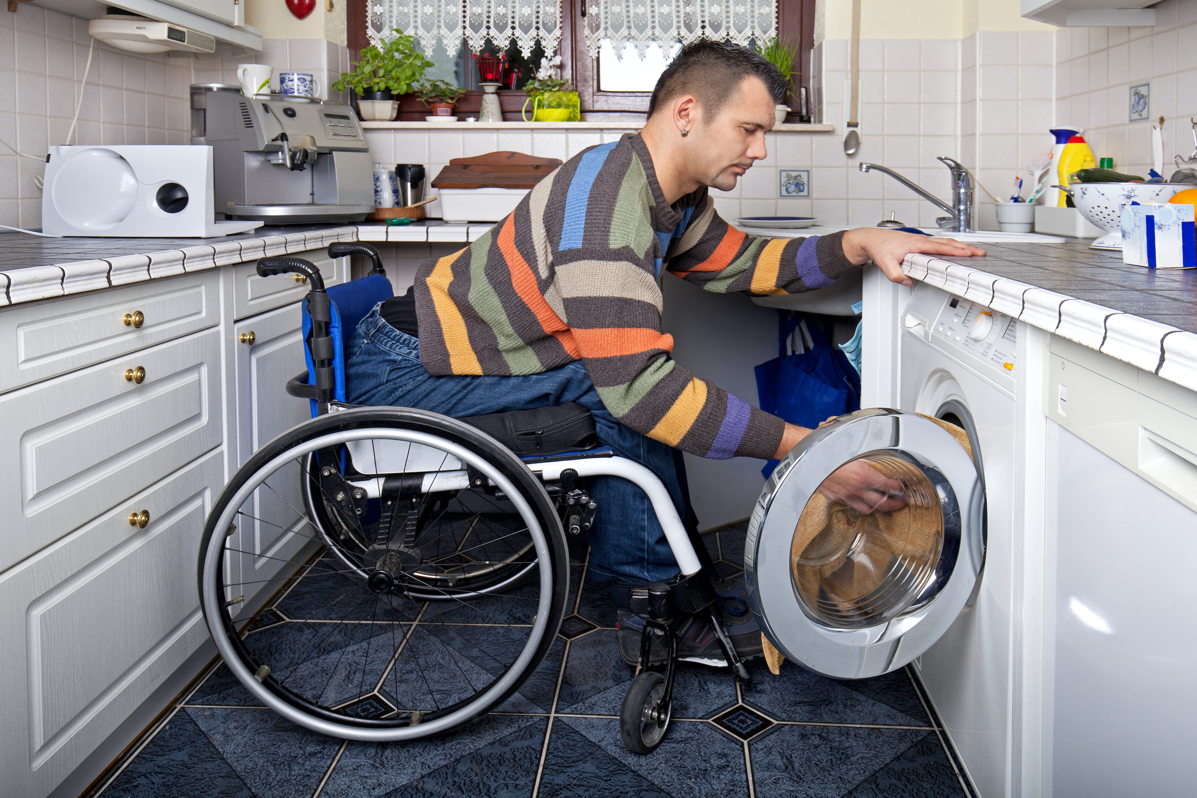 Young white male sitting in a wheelchair leaning forward reaching laundry in a front load washer.