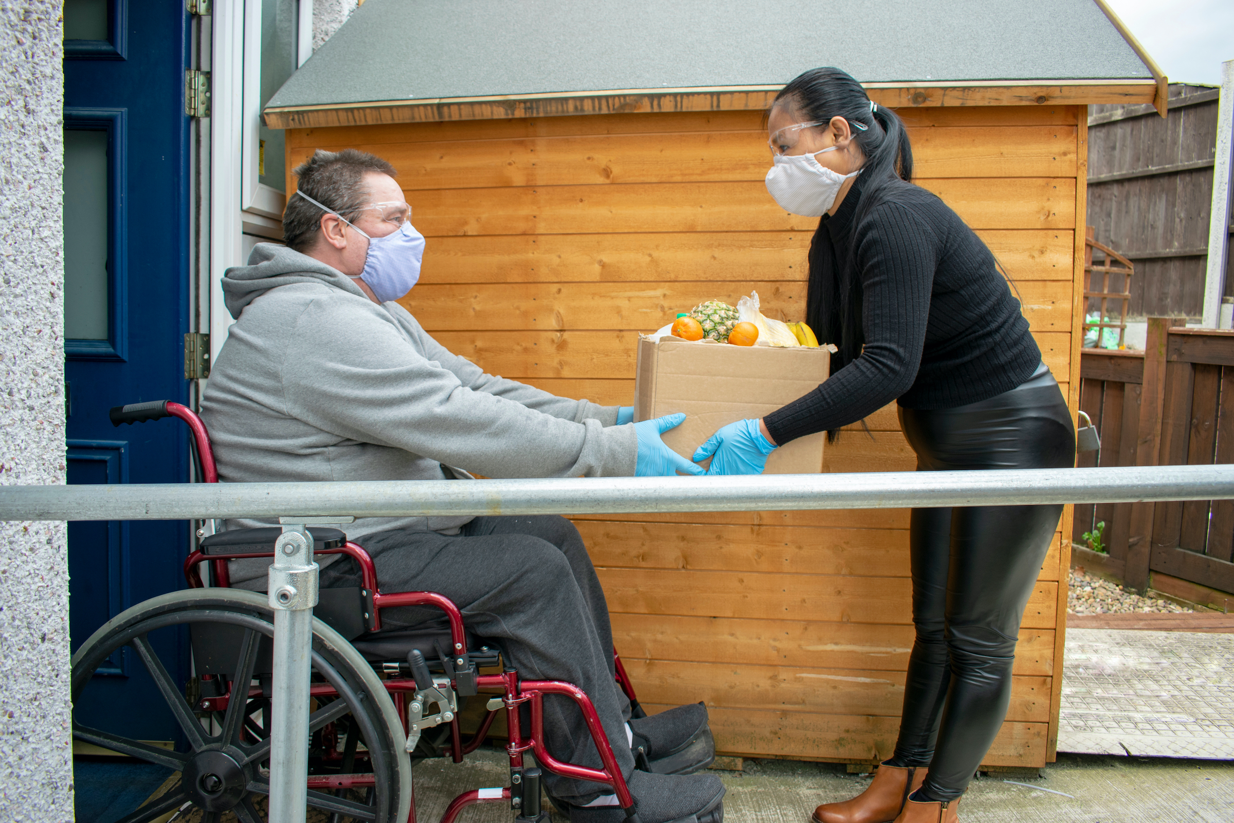 white male wearing a mask sits in a wheelchair while a woman hands him a box of groceries.