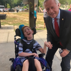 Young man in a wheelchair beside a grey headed man smiling at camera