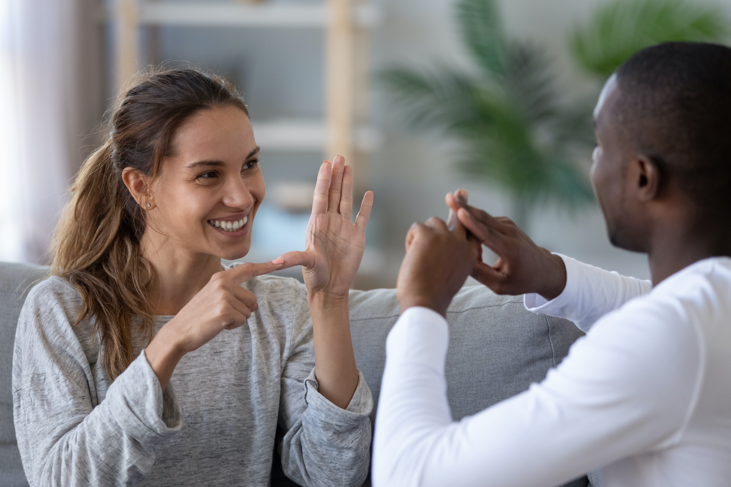 A young white woman and a young black man sit facing each other using American sign language.