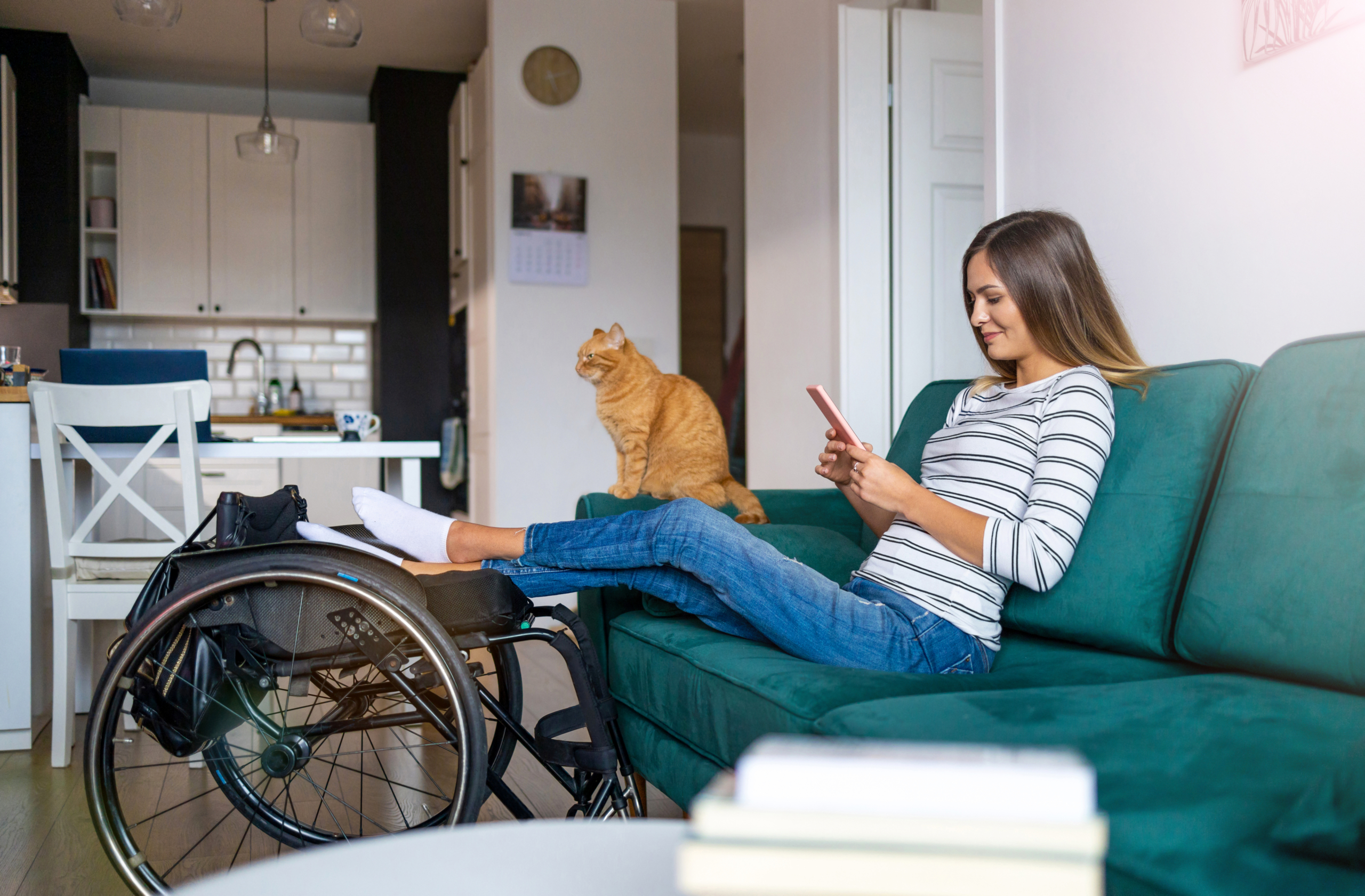 Young lady sits on a sofa looking at her phone. A cat sits on the armrest. Her legs are outstretched resting on a wheelchair.